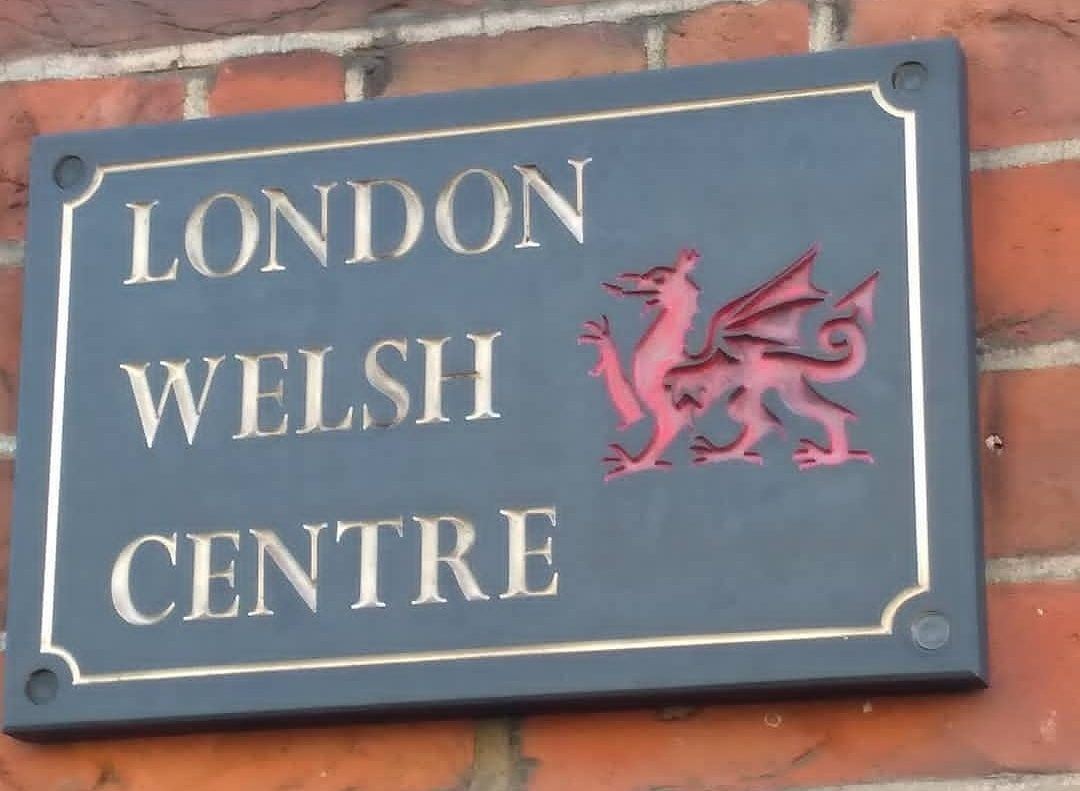 Sign reading 'London Welsh Centre' on a brick wall, with a Red Dragon on it